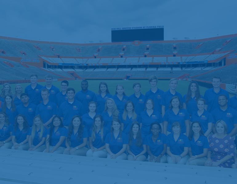 Blue filter over a photo of Florida Youth Institute participants and counselors pose wearing blue polos at the UF Ben Hill Griffith stadium.