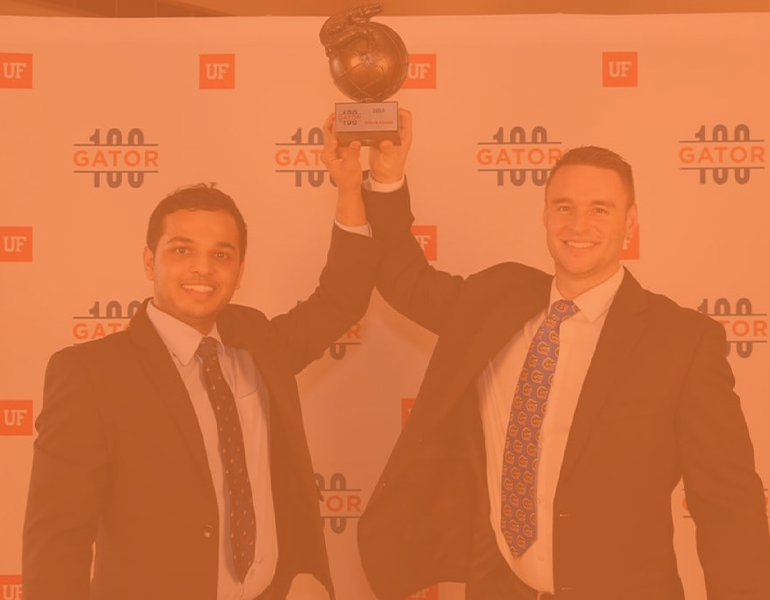 Karthik and partner, Luke, pose holding a trophy in recognition at the Gator 100 ceremony.