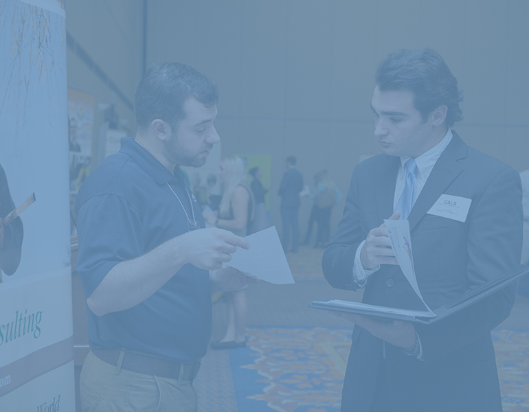 Male CALS student speaks to an employer at the CALS Career Expo