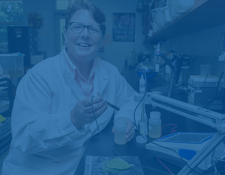 CALS professor smiling in a lab coat and gloves while performing an experiment in the lab