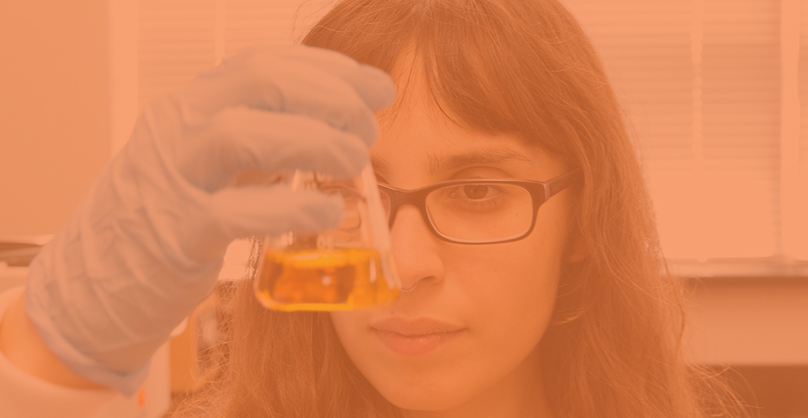 Female CALS student holding a scientific flask with yellow liquid up to eye level
