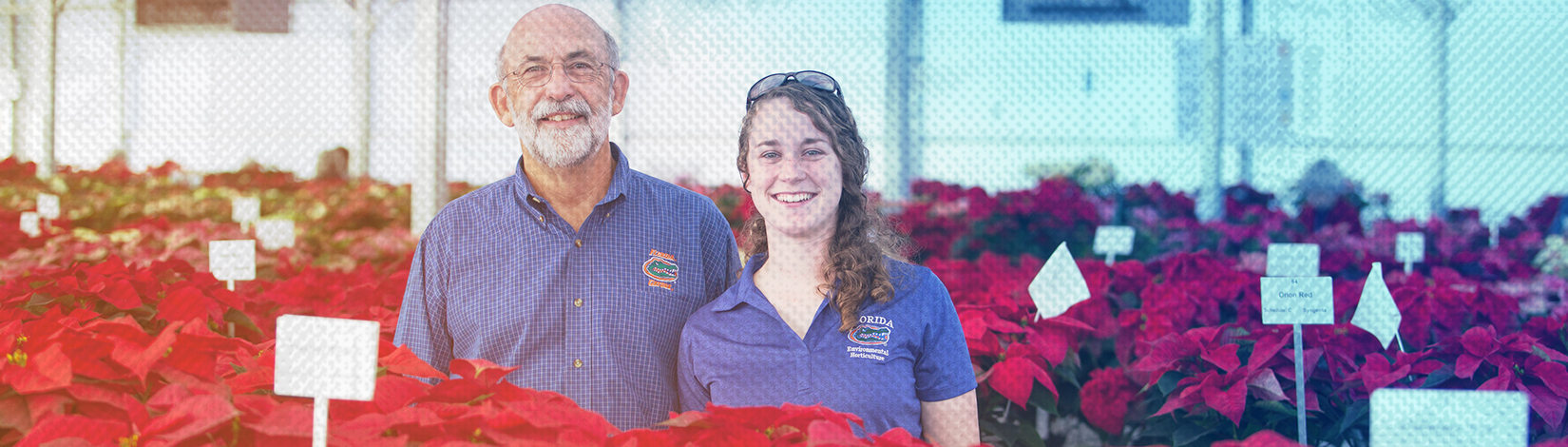 Horticulture student poses with a professor in a greenhouse full of poinsettias.