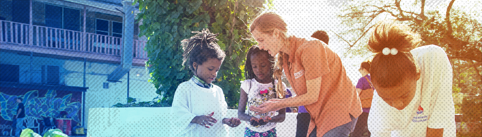 a UF/IFAS CALS student teaches three small young girls about planting seeds near a raised flower bed