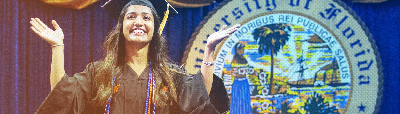 Graduating female CALS student with honors cords walks across stage waving at a graduation ceremony