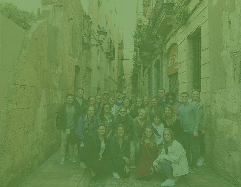 CALS Students studying abroad in Spain, posing for a group photo in the street.