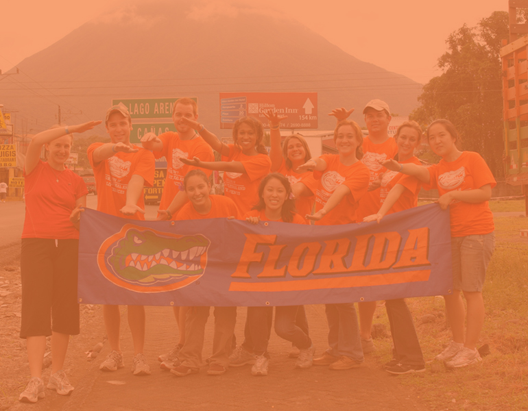 CALS students studying abroad in Peru pose for a photo with a mountainin the background, wearing matching orange gator shirts and gator chomping.