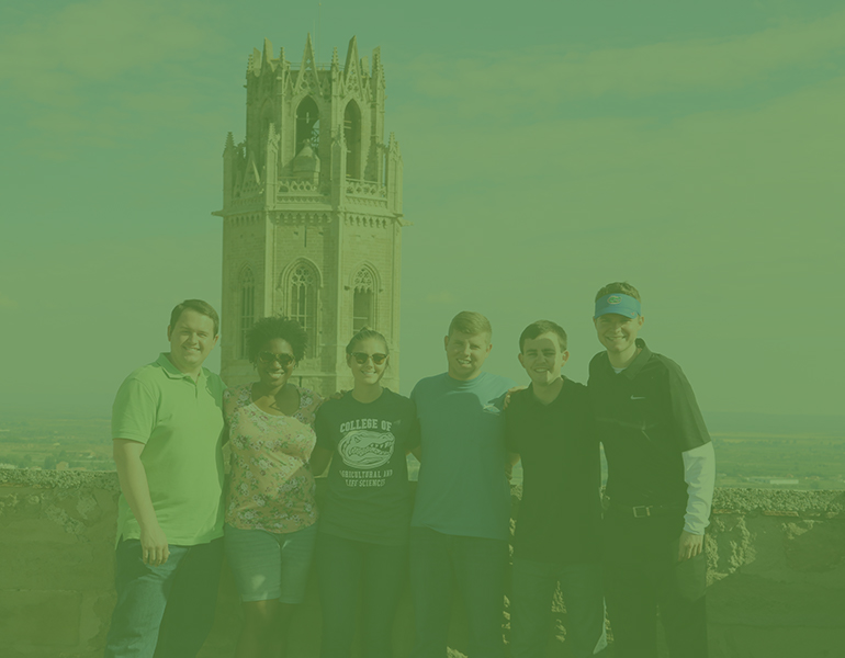 Six CALS students studying abroad in Spain posing for a picture on a city overlook with a tower int he background.