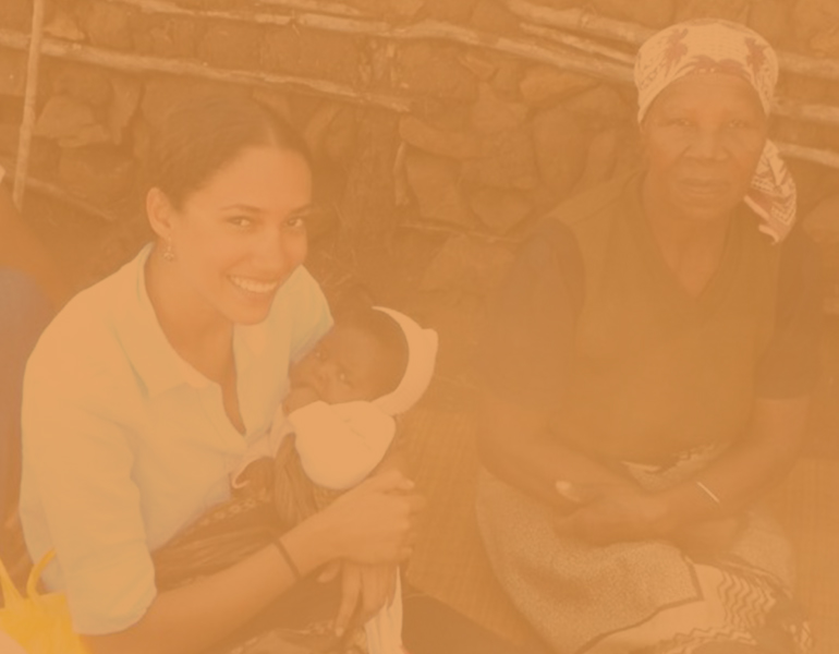 female CALS student studying abroad in Swaziland holding a child and sitting next to a local resident.