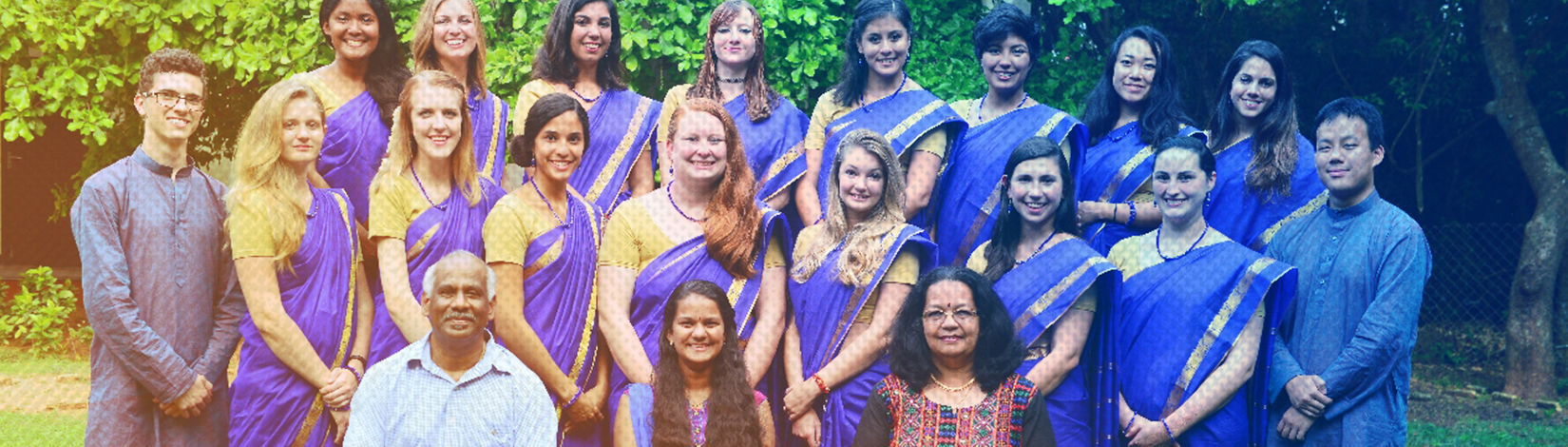 Group of CALS students studying abroad in India, posing in matching purple traditional clothing with some local residents.