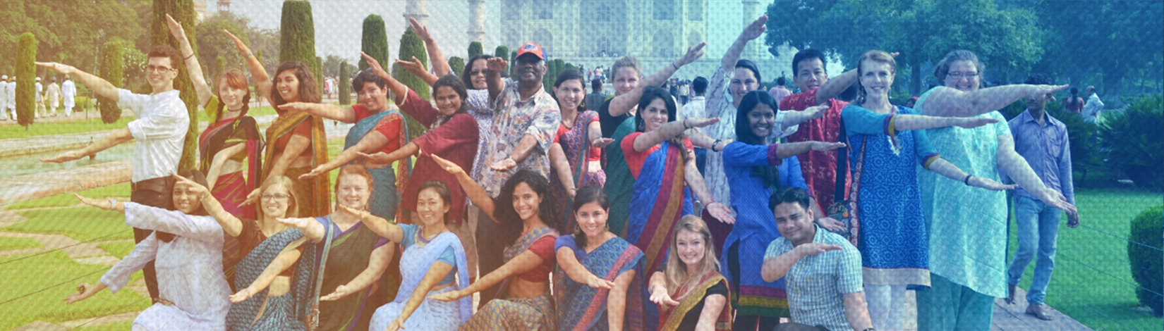 Group of CALS students studying abroad in India, wearing traditional clothing and gator chomping in front of the Taj Mahal.