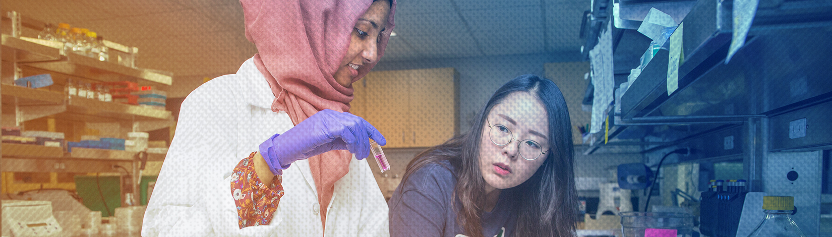 Female CALS location student wearing a white lab coat, gloves nad a headscarf pours a solution into graduated cylinders while her teacher observes.