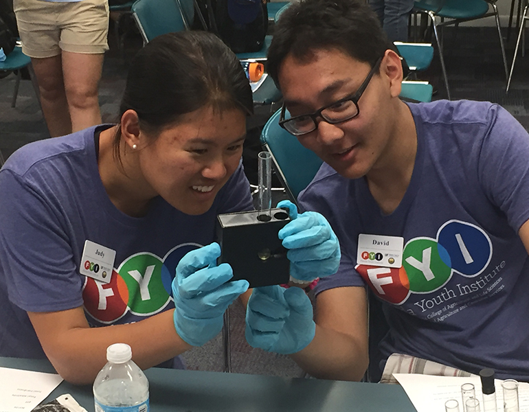Two prospective CALS students wearing gloves and FYI shirts closely observe a test tube