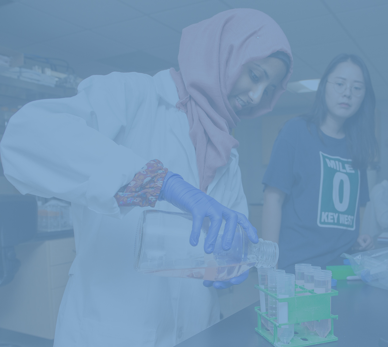 CALS student wearing a white lab coat, gloves and a headscarf pours a solution into graduated cylinders while her teacher observes.